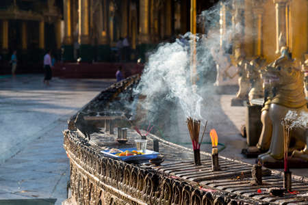 Incense burns with a tray of offerings at the Shwedagon pagoda in the early morning sun in Yangon