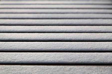 Abstract of snow on bench with only one slat in focus