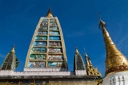 Tower depicting the life of Buddha, surrounded by spires at the Shwedagon pagoda in Yangon