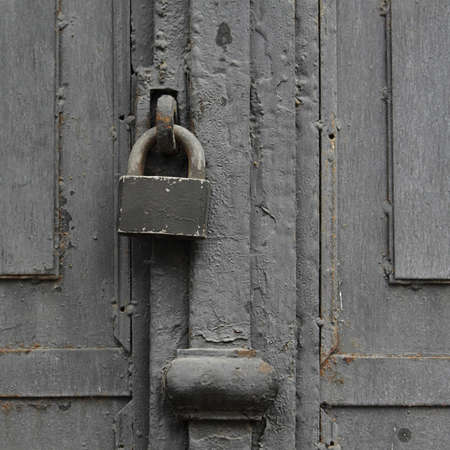 keep watch over: padlock on an old wooden door