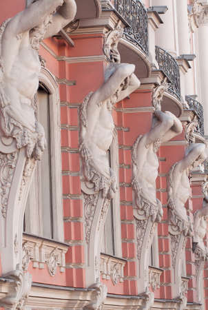 Several windows with beautiful moldings and atlantes in a historic building Stock fotó