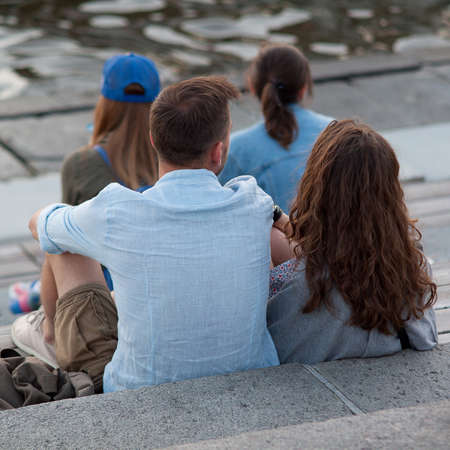 A guy and a girl and other people sit on the steps of the embankment, rest together and talk