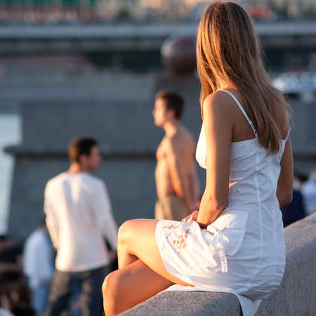 The girl sits in the rays of the evening sun on a city background 스톡 콘텐츠