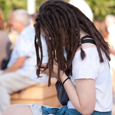 A girl with a fashionable youth haircut from dread sitting and communicate on her mobile phone