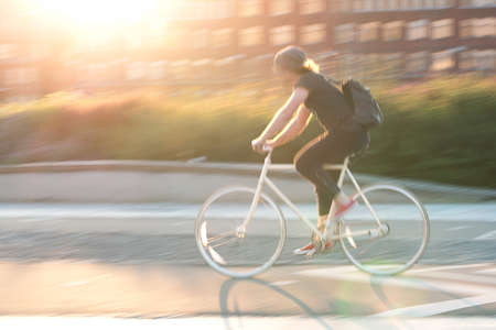 the guy rides a bike around the city on a sunny summer day