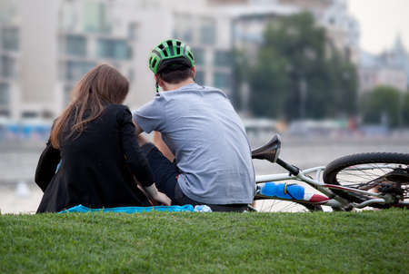 A boy and a girl rest together and spend time after work or study in a summer city