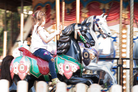 Little girl is riding a horse on a carousel