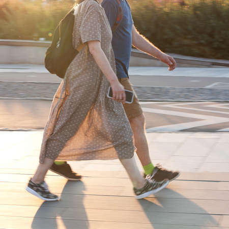 A boy and a girl are walking along the sunny spring city 스톡 콘텐츠