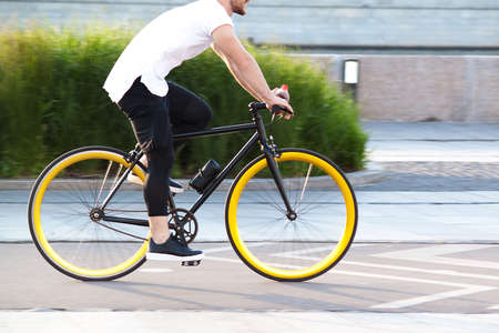 modern sports guy cycling through the summer city
