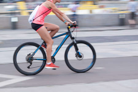 the girl rides a bicycle through the summer city