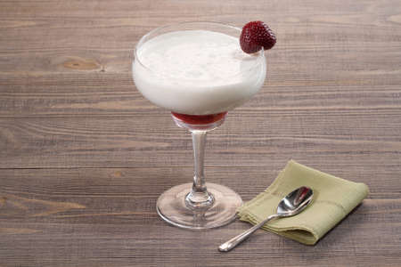 Strawberry with ice cream in a glass on a wooden table