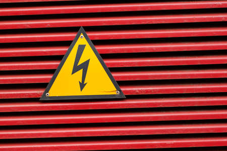 high voltage sign on a bright red surface