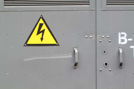 warning sign cautiously high voltage on the metal door of the technical room 版權商用圖片
