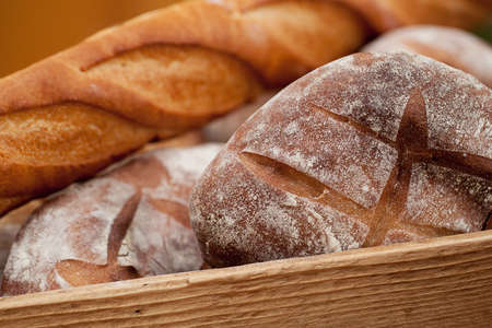 several rye bread buns and a wheat baguette lie in a wooden box