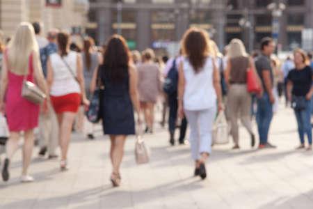 Menschen machen einen gemütlichen Spaziergang durch die sonnige Sommerstadt, ein verschwommener Hintergrund