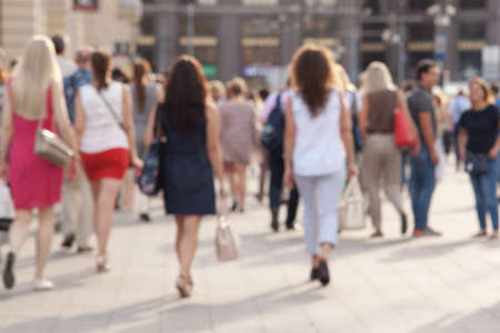 mensen maken een ontspannen wandeling door de zonnige zomerstad, een onscherpe achtergrond