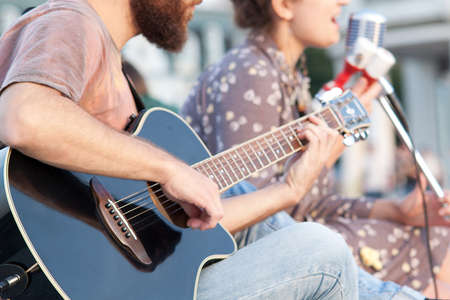 boy and girl sing a song on the street, girl sings, boy plays guitar