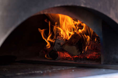 oven with burning firewood and bright tongues of flame heated for cooking pizza and other tasty products