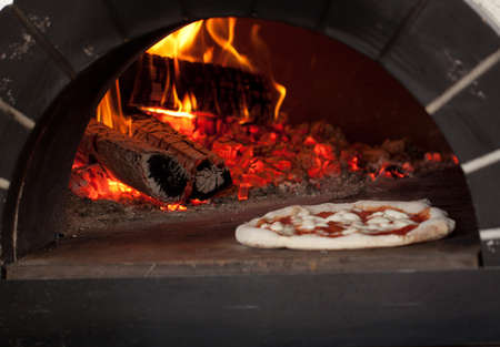in the wood burning stove over an open fire on charcoal, prepare delicious traditional Italian pizza Stock Photo