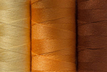 beautiful background of three spools of cotton thread of natural colors - yellow, orange, brown