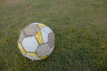dirty football: dirty soccer football and on green grass field