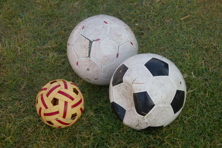 dirty football: dirty soccer football and sepak takraw on green grass field