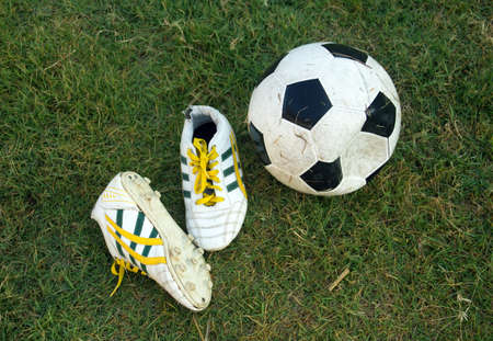 football shoes: old soccer football and football shoes on green grass field