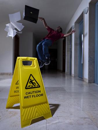 Man slips next to Wet Floor sign photo