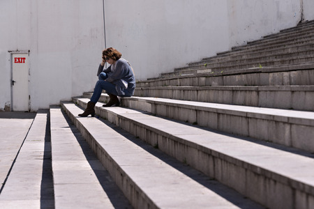 mature women only: Woman sat in a few stairs, looking down