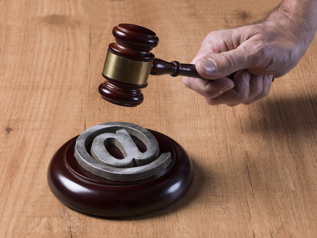 sentencing: Judge gavel, knocking over a at symbol, on a wooden background