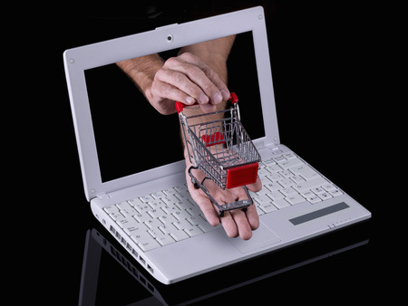 Hand reaches out of a laptop with a shopping cart photo