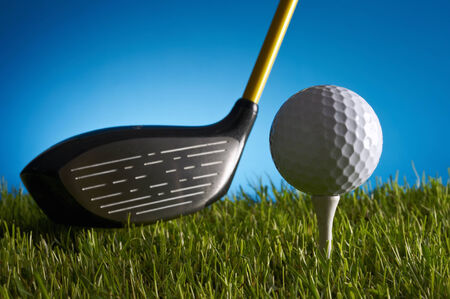 golf stick: Golf stick and ball on grass, with a blue background.