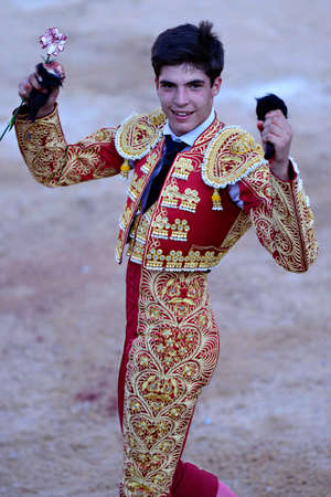 over burdened: Bullfighter an ear of the bull in hand, celebrating success Stock Photo