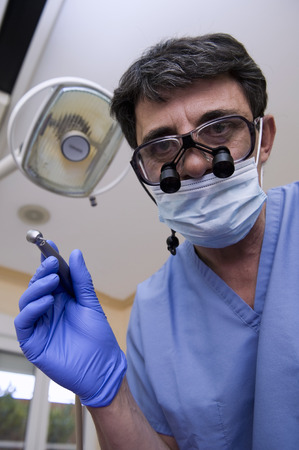 surgical coat: Dentist with special glasses holding a lathe in his hand