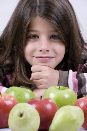 8 years: Portrait of 8-year-old girl with apples and pears Stock Photo
