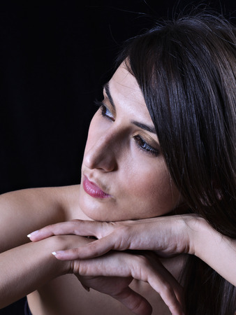 Portrait of a young woman with hands on chin photo