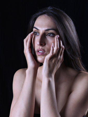 Portrait of a young woman with hands on face photo