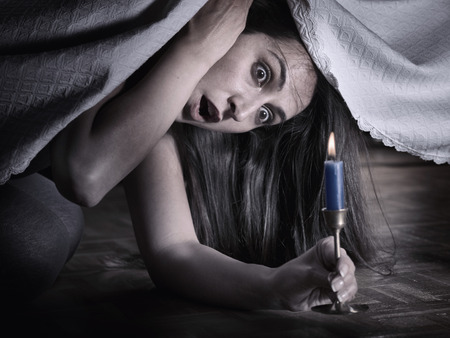 A young woman fear, looking under the bed and surprised at what she sees Stock Photo