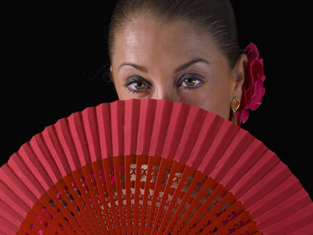 flemish: Closeup of a Flemish woman, from behind a hand fan, looking at the camera