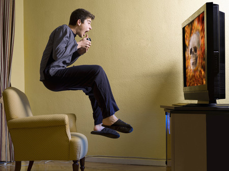 video game: Young, playing a video game, jumping to panic Stock Photo