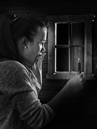 half open: young woman looking through a window, looking surprised