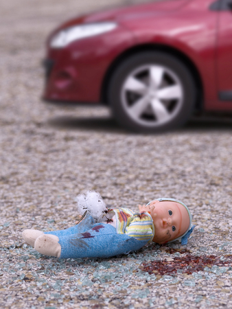 abandoned car: Closeup of a broken doll and bleeding on the asphalt and broken glass of a vehicle. Stock Photo