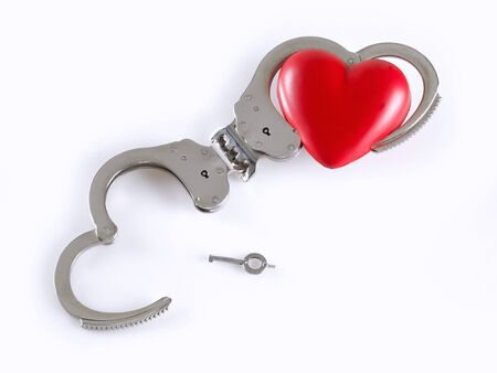 key to freedom: Handcuffs on white background, and a heart on one end. Divorce concept
