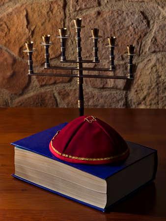 yarmulke: Menorah, talmud and kippah on a wooden table