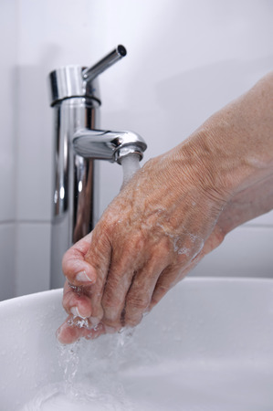 Rinse hands under a faucet with the water falling photo