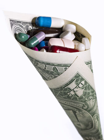 high cost of healthcare: A one-dollar bill rolled into a cone full of medicines