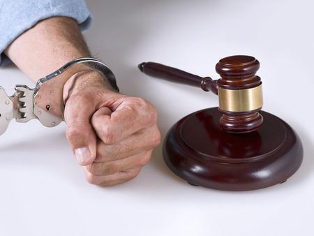 criminal activity: A hand handcuffed next to a gavel