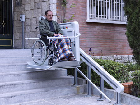 Man in wheelchair on a platform, climbing some stairs Stok Fotoğraf - 36499283