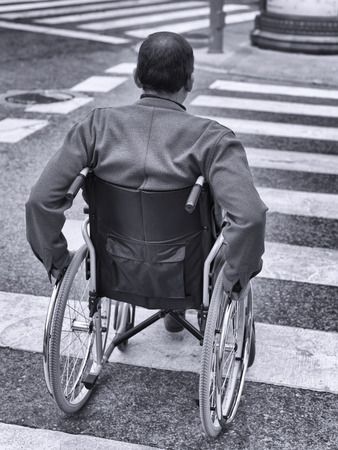 immobility: Man in wheelchair crossing a zebra Stock Photo