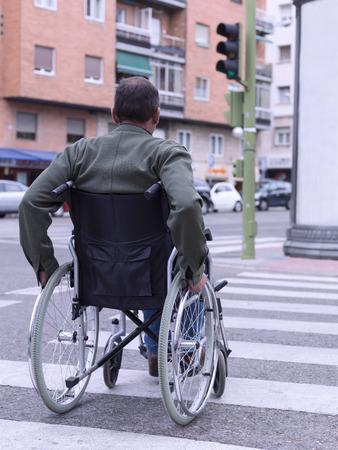 Man in wheelchair crossing a zebra Stok Fotoğraf